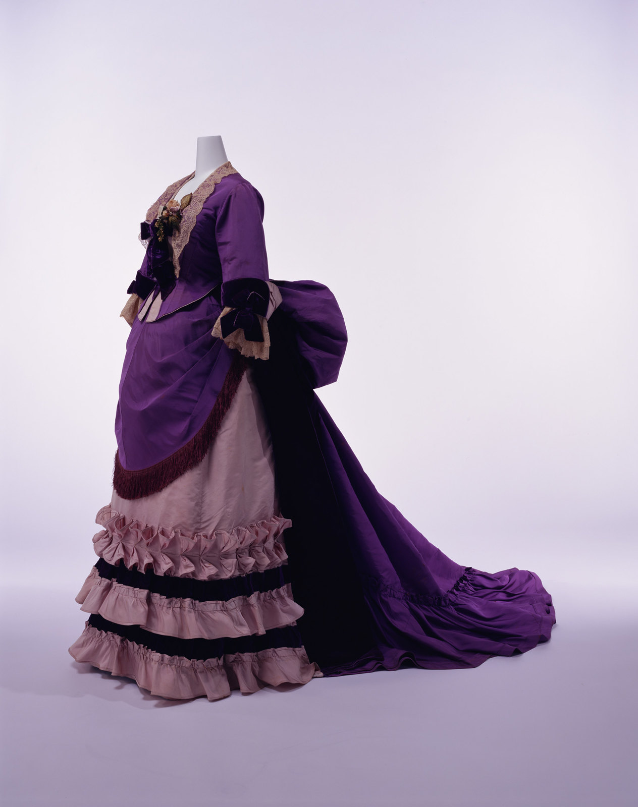 1894. Afternoon Dress. Silk faille set of bodice and skirt; silk lace and velvet bows at neck and cuffs; apron-shaped overskirt with silk fringe at front. Credit KCI
