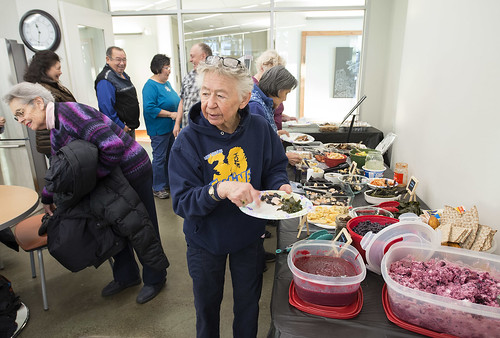 Mary Lou Bottorff prepares a plate of food for her grand daughter as others move through the line. Bottorff spends several days preparing food in advance of the potluck and has played a big role in bringing people together for the monthly event.