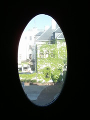 symmetry(0.0), porthole(0.0), fisheye lens(0.0), reflection(0.0), circle(0.0), lighting(0.0), arch(1.0), window(1.0), sunlight(1.0), photograph(1.0), light(1.0), glass(1.0), green(1.0), darkness(1.0),