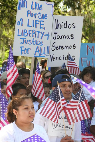 People at an immigration rally hold American flags