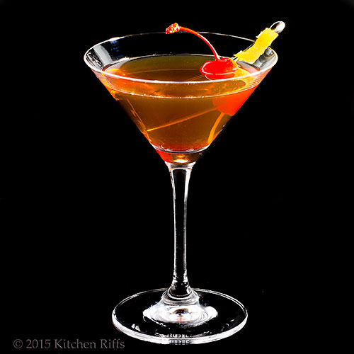 The Bijou Cocktail in cocktail glass with maraschino cherry and lemon twist garnish
