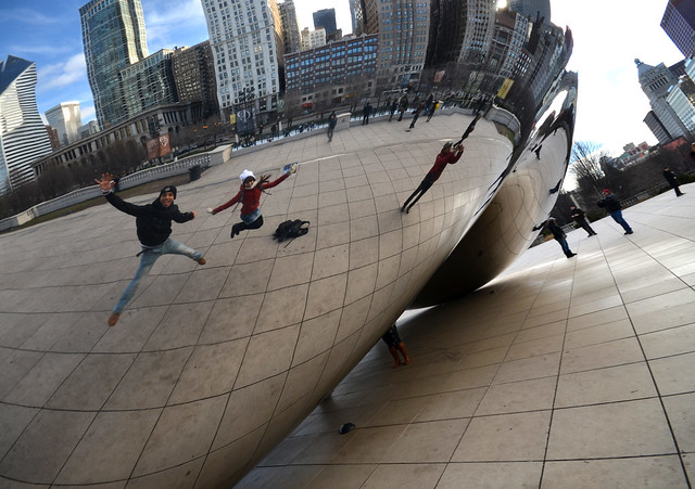 Saltando en el aire con los brazos abiertos frente al Cloud Gate de Chicago