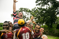 Tom Tomaney, assigned to the hospital ship USNS Mercy (T-AH 19), is lifted by the Nabua Broncos rugby team after a scrimmage during Pacific Partnership 2015. (U.S. Navy/MC2 Mark El-Rayes)