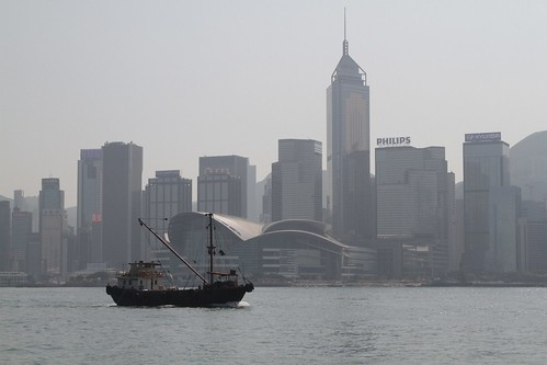 Small cargo boat passes the Hong Kong skyline