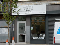 "A ground-floor terraced shopfront with a small tree and a few traffic cones outside.  The right-hand side of the shopfront is shuttered, leaving only a narrow window and door on the left.  Above this left-hand side is a sign reading ""Oliver Gold / Estate Agents"" in black text on a white background."