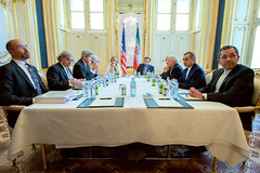 U.S. Secretary of State John Kerry - flanked by National Security Council Senior Director for Iran, Iraq, Syria and the Gulf States Robert Malley, U.S. Energy Secretary Dr. Ernest Moniz, Under Secretary of State for Political Affairs Wendy Sherman, and European Union Deputy Secretary General Helga Schmid - sits across from Iranian Foreign Minister Javad Zarif, Dr. Ali Akbar Salehi, the Vice President of Iran for Atomic Energy and President of the Atomic Energy Organization of Iran, and other advisers on July 2, 2015, in Vienna, Austria, before resuming negotiations about the future of Iran's nuclear program. [State Department Photo / Public Domain]