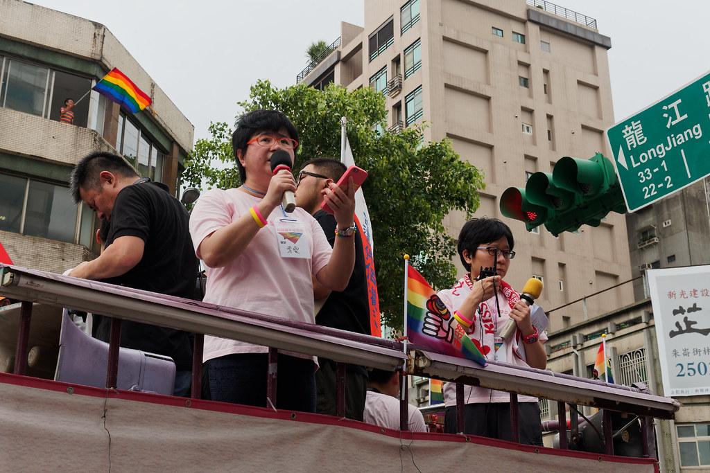 伴侶盟秘書長簡至潔(右起)、理事長許秀雯呼籲朝野立委通過婚姻平權法案,長年爭取同志權益的祁家威則在後方大樓揮舞著彩虹旗。(攝影:林佳禾)