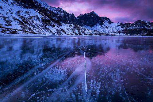 ice eis skating eislaufen melchsee frutt innerschweiz central switzerland schweiz berge mountain bergsee lake sunset sonnenuntergang bubbles luftblasen leading lines reflection reflektion bergkette brunzo lini schwarzeis pink
