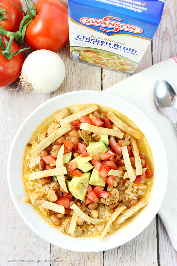 Mexican Chicken and Rice Soup in a white bowl with fresh vegetables and a carton of Swanson Chicken Broth.