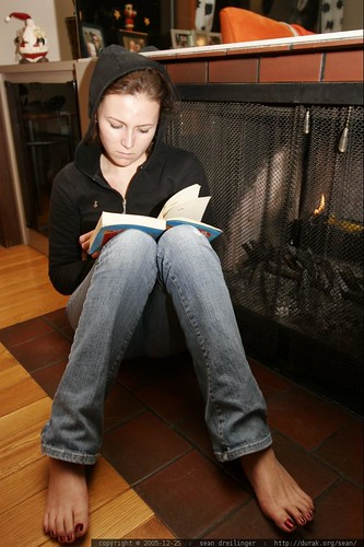 megan, barefoot by the fire, reading fast food nation