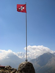 swiss flag in front of mountains