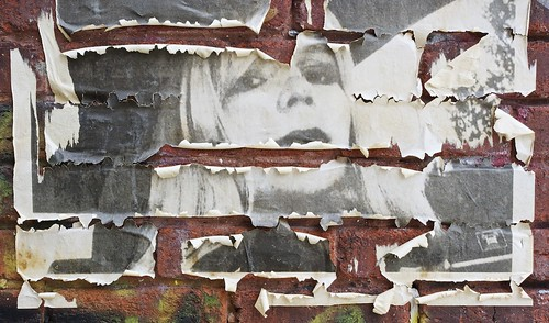 A weather-worn poster of Chelsea Manning on a brick wall in Montreal