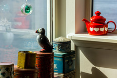 Puffin, jars and a red teapot by a window in Velbastaður, Faroe Islands