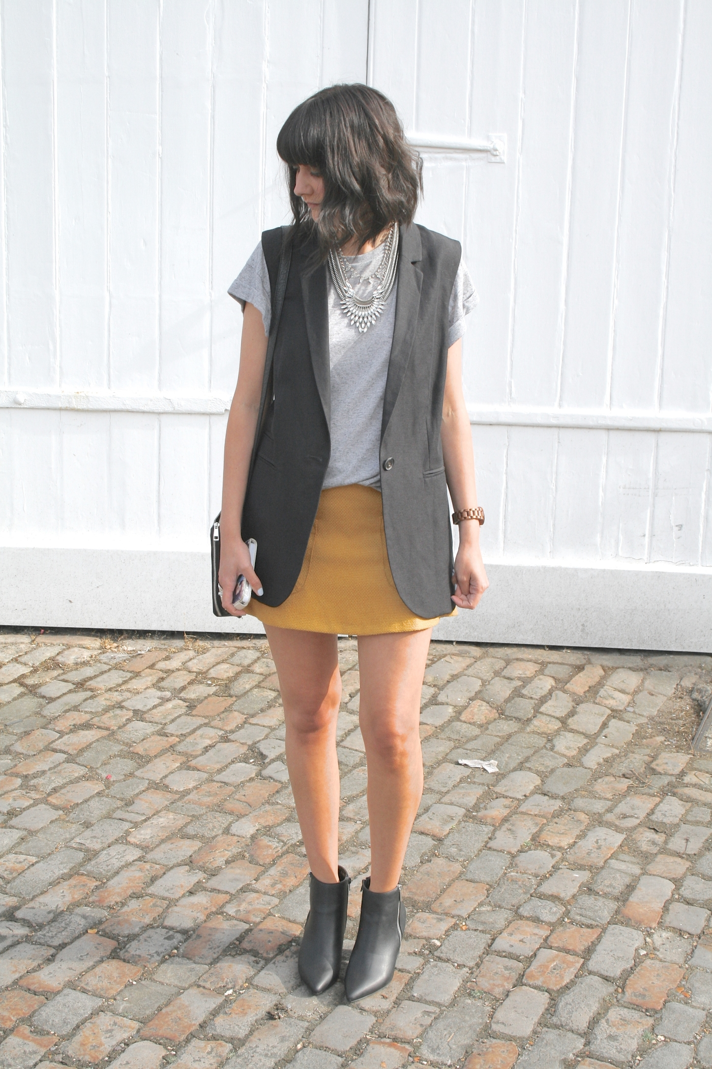 black waistcoat, grey tshirt and yellow skirt