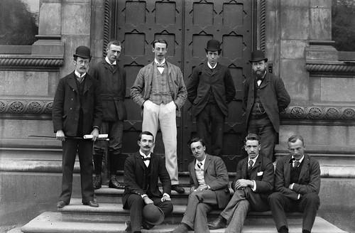 9 men in front of ornate door, Trinity College, Dublin