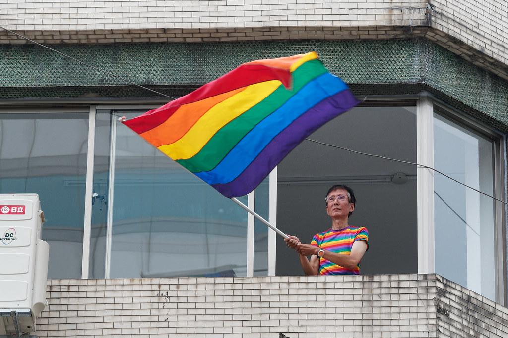 長年爭取同志權益,也為同志婚姻平權二度聲請大法官釋憲的祁家威,在遊行活動的各地點揮舞著彩虹旗。(攝影:林佳禾)