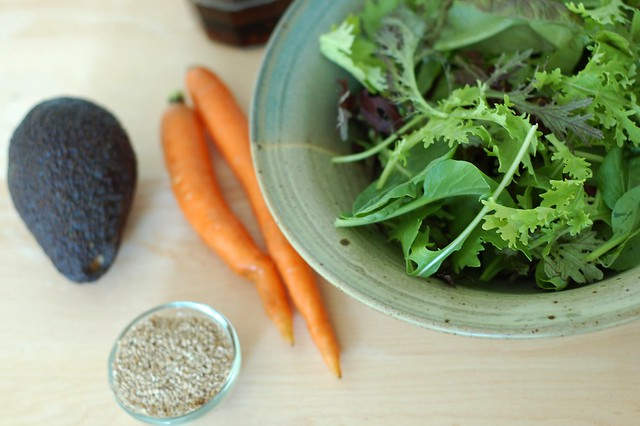 Ingredients for a salad of spicy baby greens with carrot matchsticks, avocado and a sweet ginger sesame dressing by Eve Fox, the Garden of Eating, copyright 2015