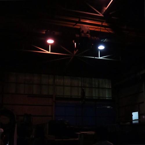 工場を照らす水銀灯の光、徐々に明るく。