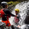 Adventure group gorge walking in the Brecon Beacons National Park in Wales. An unorthodox way of taking a shower!