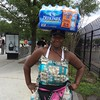 The women selling water near the DC armory can carry a whole case on her head!