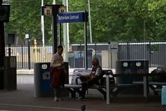 Man praat met jongen op station
