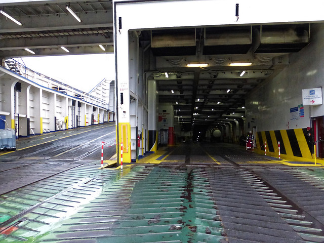 Stena Mersey - View from the stern ramp of the main vehicle deck and the ramp leading to the upper vehicle decks (on the left). Just visible in the centre is the raised door to the lower hold (the row of lights in the background of the picture).