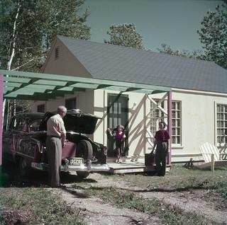 Man, woman and little girl take possession of their tourist cabin in Riding Mountain National Park, Manitoba... / Un homme, une femme et une petite fille prennent possession de leur cabine de touriste au Parc national du Mont-Riding, au Manitoba...