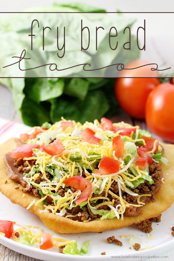 Fry Bread Tacos on a white plate with fresh vegetables.