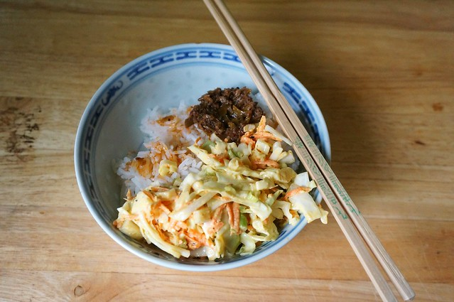 Classic mustard coleslaw in a blue and white porcelain bowl with warm rice and Chinese pickles (don't knock it till you've tried it). A pair of chopsticks rests on the rim of the bowl.