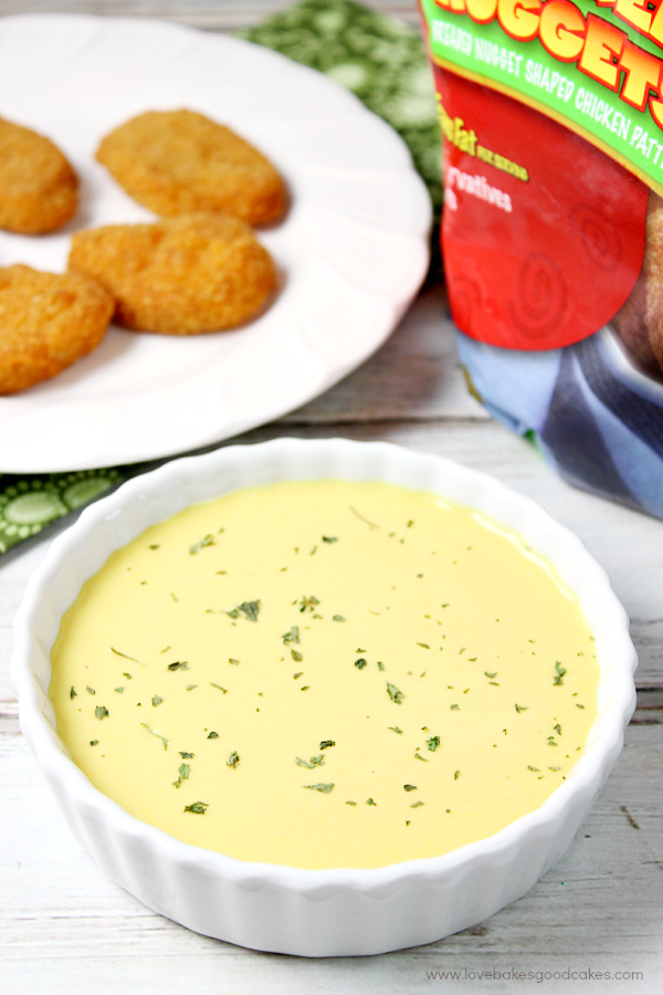 Honey Mustard Dipping Sauce in a white bowl with chicken nuggets.
