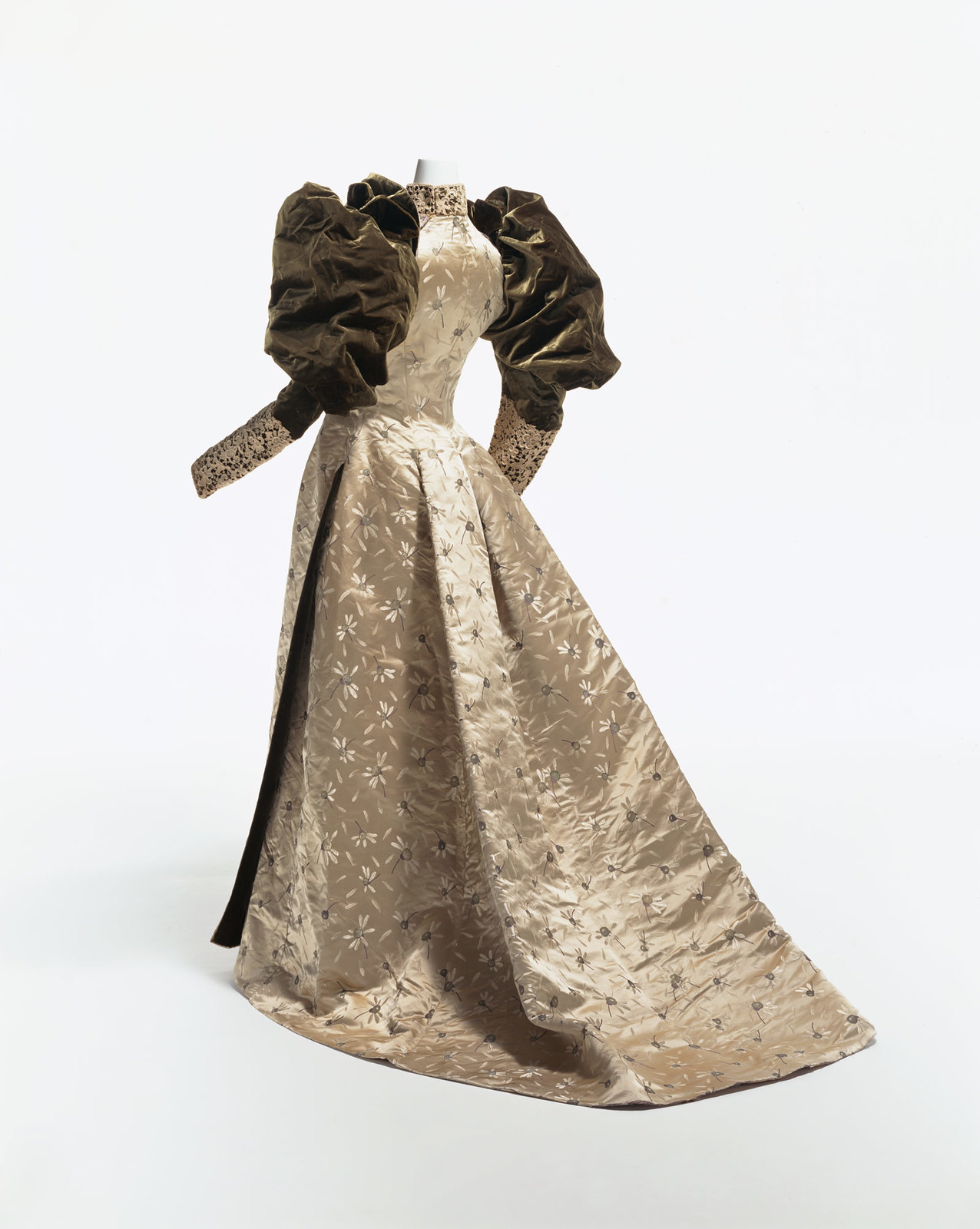 1892. Dinner Dress. silk satin with woven chrysanthemum pattern; large velvet gigot sleeves; lace decoration on cuffs and collar. KCI