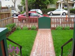 backyard(0.0), outdoor play equipment(0.0), porch(0.0), deck(0.0), playground(0.0), outdoor structure(1.0), garden(1.0), picket fence(1.0), yard(1.0), cottage(1.0), lawn(1.0), walkway(1.0),