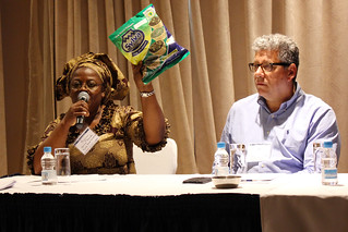 Woman dressed in traditional Zambian clothing holds bag over her head and speaks into microphone, seated next to a man.