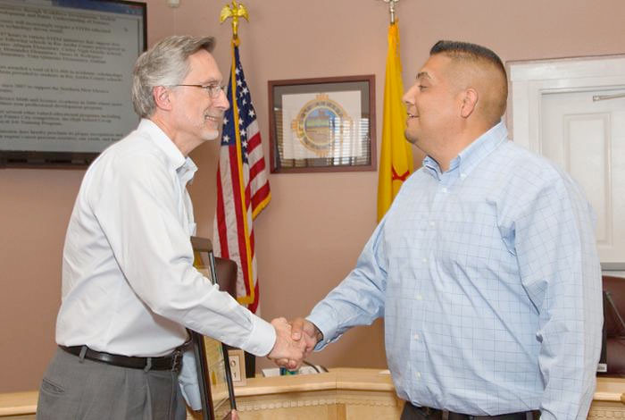 Laboratory Director Charles McMillan (left) shakes hands with Rio Arriba County Commission Chair Barney Trujillo during a Rio Arriba County Commission meeting in Española.