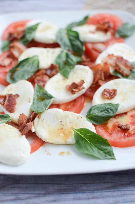 Caprese Salad with Warm Bacon Dressing - the classic combination of tomatoes, fresh mozzarella, and basil with a deliicous warm bacon dressing drizzled over top.