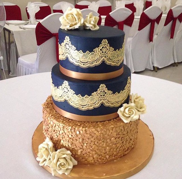 3 Tier Navy Vanilla Cake with Gold Lace, Sequins and Ivory Roses from Cakes By Hassan