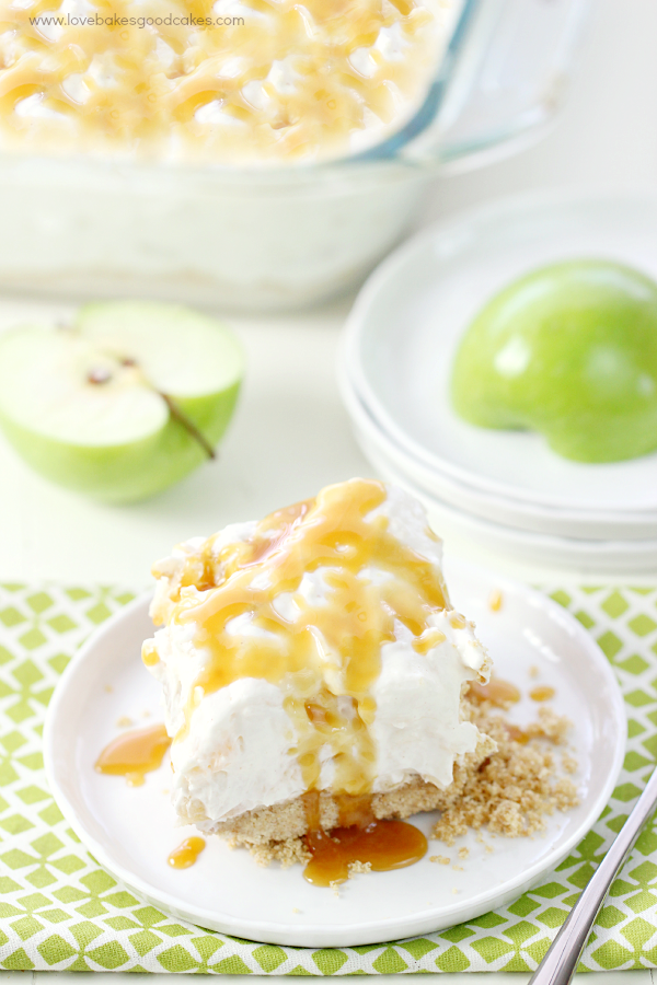 No-Bake Caramel Apple Cheesecake on a plate with green apples and a fork.