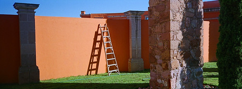 An orange wall with a ladder near the aqueduct in Zacatecas, Mexico