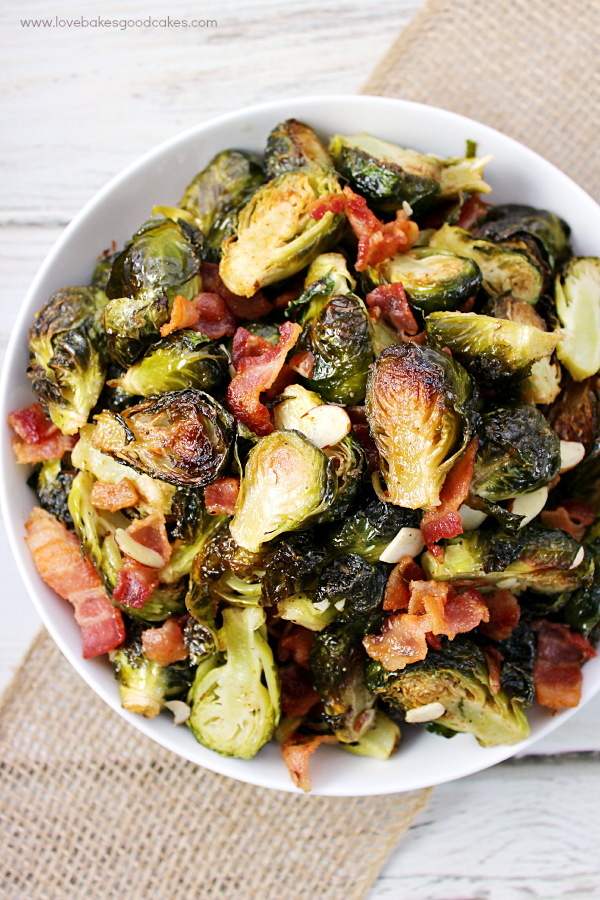 Roasted Brussels Sprouts with Bacon & Almonds in a white bowl looking down.