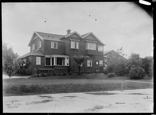 A large two-storied wooden house with a corrugated...