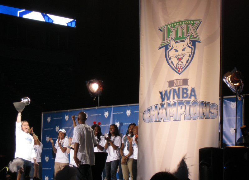 Coach Reeve holding the trophy on a stage with players in the background