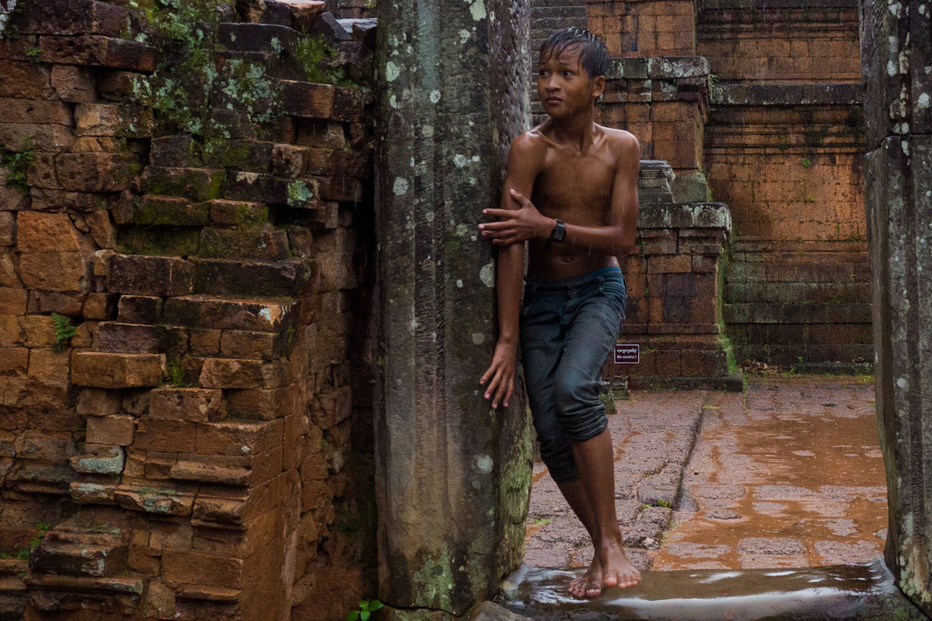 Pre Rup Temple boy plays hide and seek in the rain at Angkor Wat in Siem Reap, Cambodia in the rain at Angkor Wat in Siem Reap, Cambodia