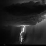 7. September 2015 - 20:00 - A rotating thunderstorm spits out a single cloud-to-ground bolt of lightning during a torrential monsoon thunderstorm.