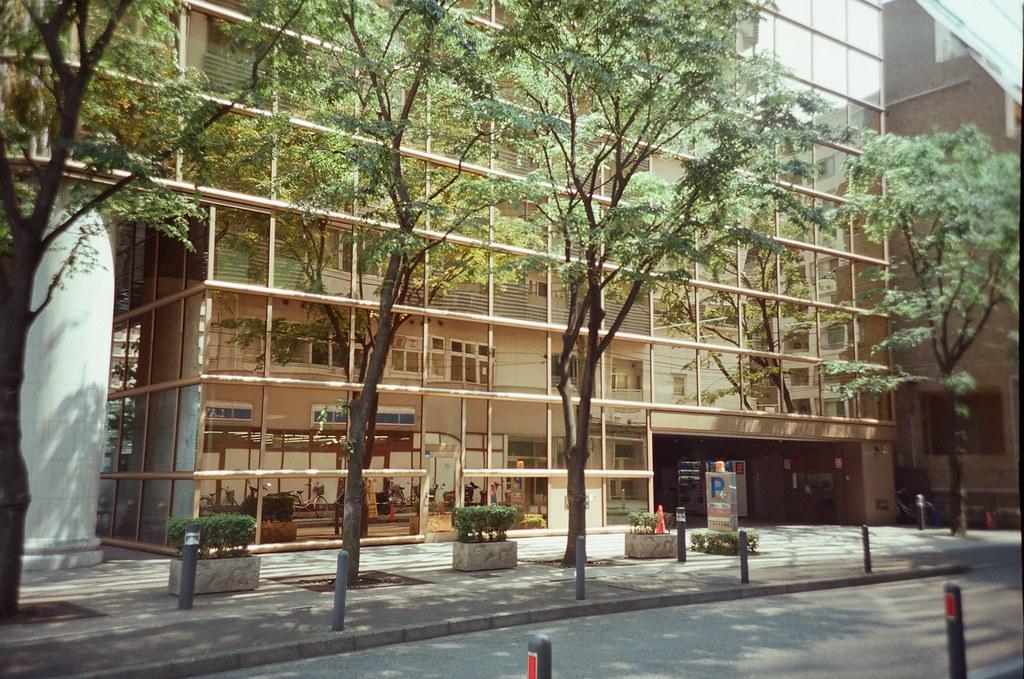 橫濱 Yokohama, Japan / Fujifilm 500D 8592 / Lomo LC-A+ 那時候從赤倉庫離開後,就這樣用走的往橫濱中華街的方向前進,一路上就慢慢走、慢慢拍。  有棟大樓外的玻璃是銅黃色,反射整個場景就很漂亮。  連人行道上的路樹都看起來搭配的剛剛好。  Lomo LC-A+ Fujifilm 500D 8592 7394-0031 2016-05-21 Photo by Toomore