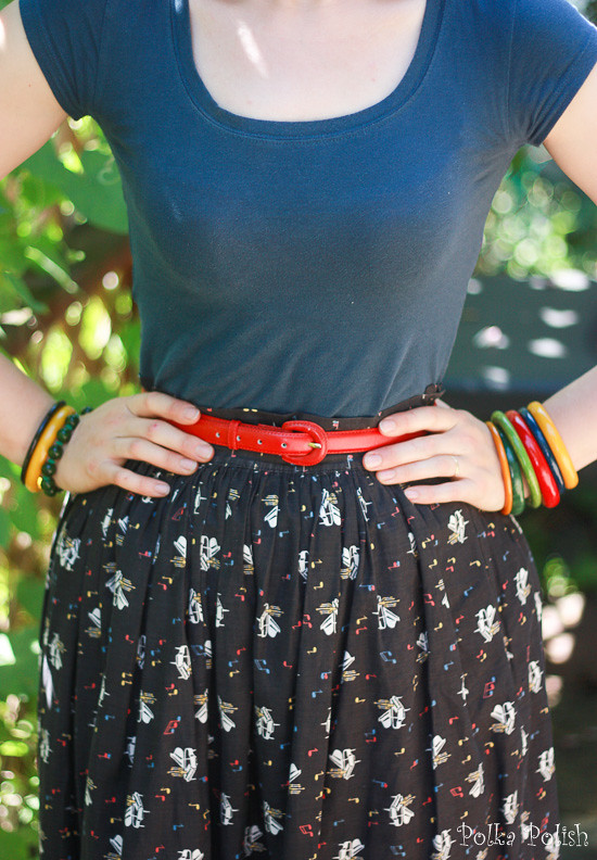 Novelty print piano skirt, brightly colored bakelite bangles, modern blue t-shirt and a red belt