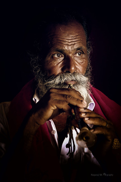 An old man from tribal community playing musical instrument