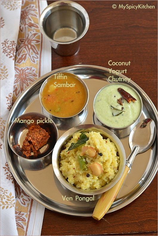 A platter of South Indian breakfast consisting of kara pongal, coconut chutney, tiffin sambar and mango pickle.