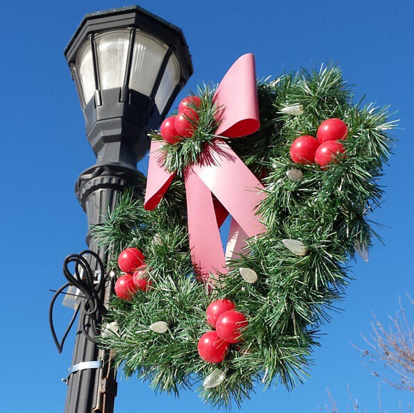 artificial greenery with four sets of three red ornaments, and a now-pink bow on top
