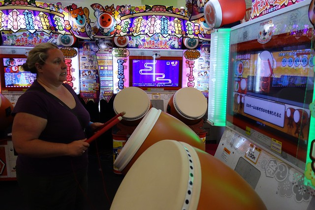 Claire playing the drums in an arcade