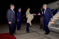 Chilean Ministry of Foreign Affairs Director of Protocol Ambassador Gloria Navarrette, Commander of Chilean Air Force Stations for Santiago Hugo Rodriguez Gonzalez, and U.S. Ambassador to Chile Mike Hammer greet U.S. Secretary of State John Kerry as he steps off his airplane on October 4, 2015, after arriving in Santiago, Chile, en route to the 2015 Our Ocean conference in Valparaiso, Chile. [State Department photo/ Public Domain]
